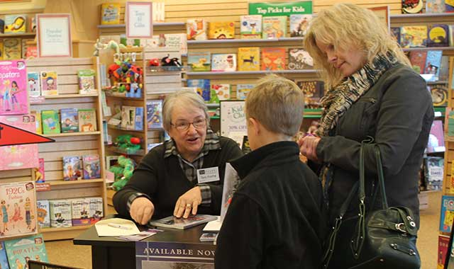 Author Toni Rocha signs a book for Joseph Ott and his mom, Amy Ott, at Barnes & Noble at CherryVale Mall in Cherry Valley, Ill. (Blake Nunes photo)
