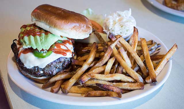 The Jovany Mexican Burger is topped with pepper jack cheese, jalapenos, sliced onion, Sriracha sauce, avocado and chipotle mayo.